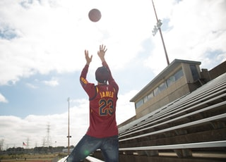man in orange and white basketball jersey shirt and blue denim jeans jumping on air