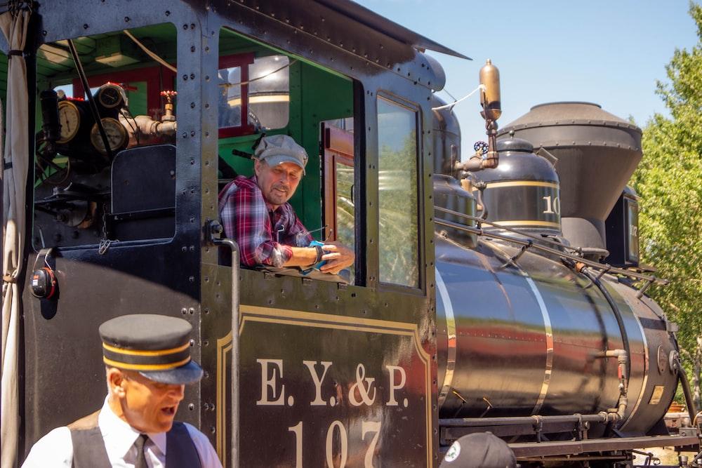 man in purple dress shirt standing beside train during daytime
