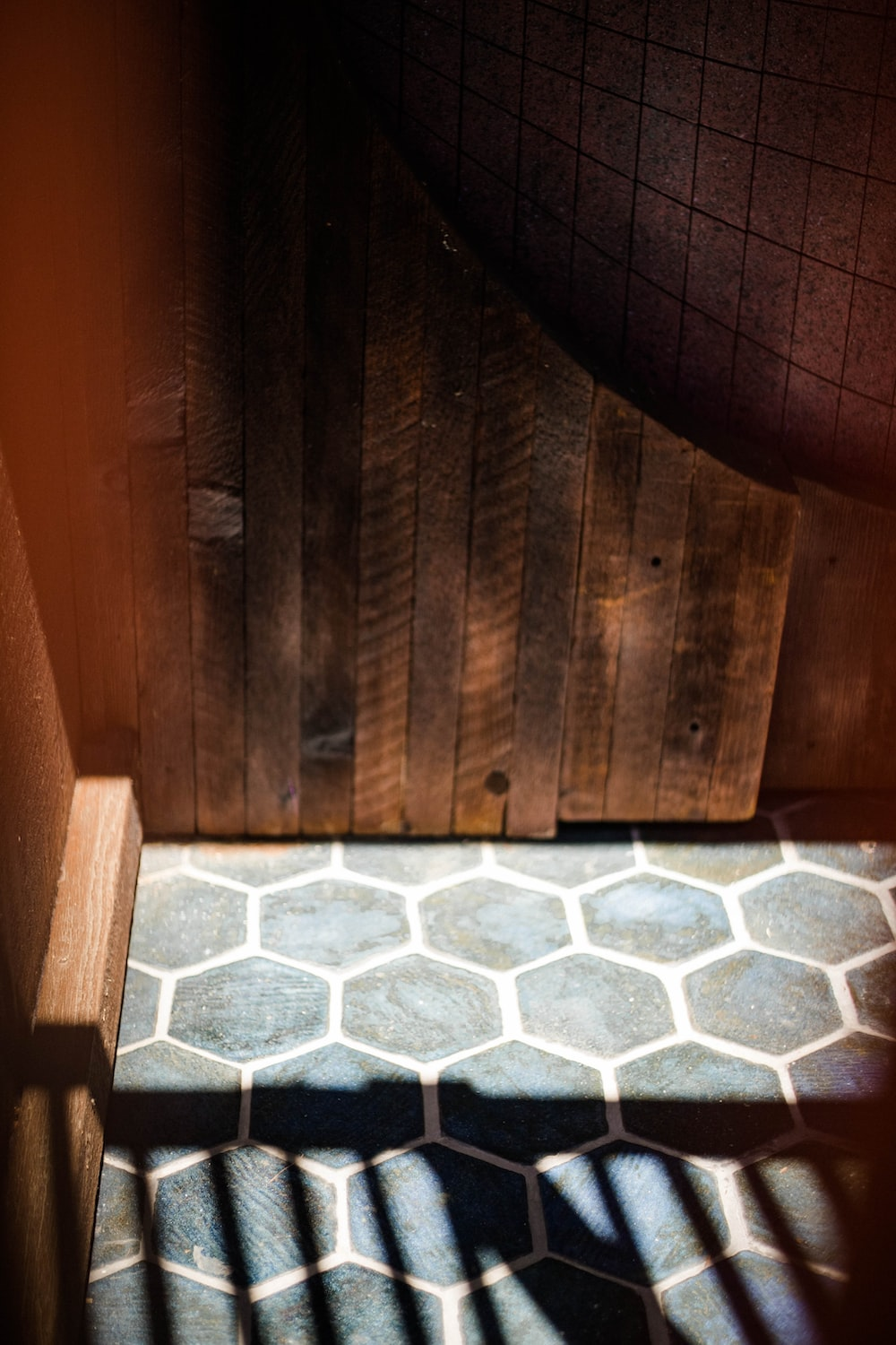 brown wooden wall with white and gray floor tiles