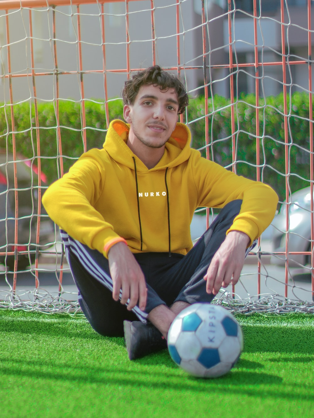 boy in yellow sweater and black pants sitting on soccer goal net