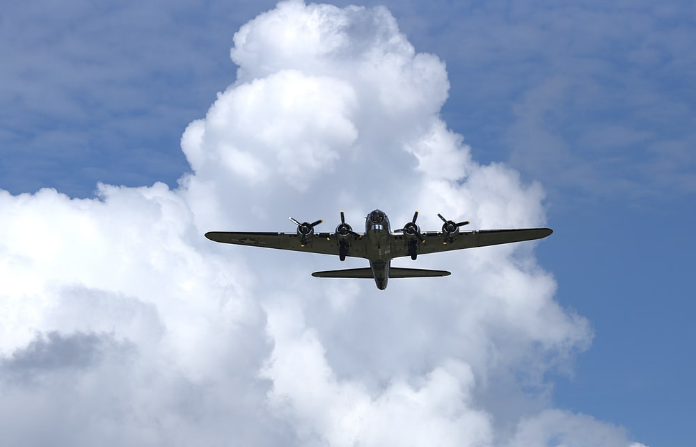 black jet plane flying under white clouds during daytime