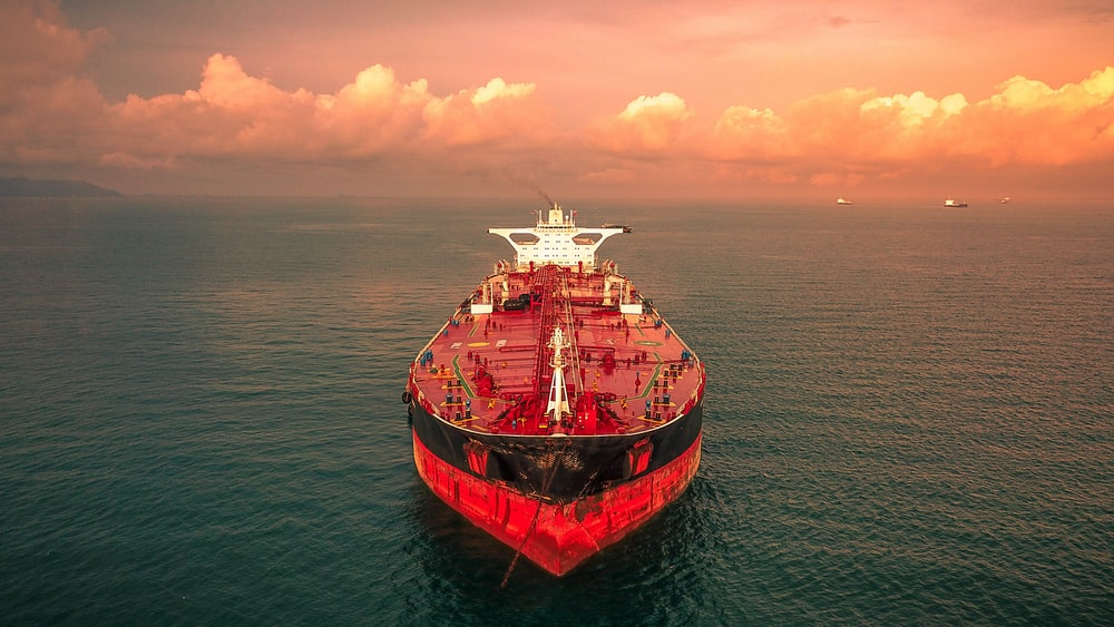 red and white ship on sea under cloudy sky during daytime