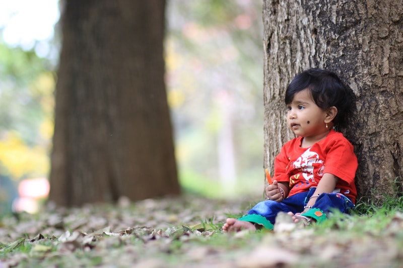 girl in red shirt sitting on ground with dried leaves