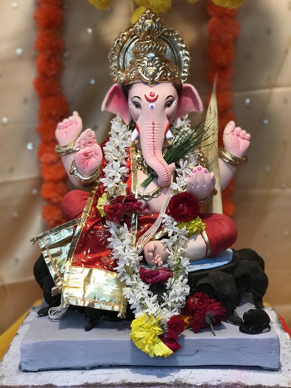 gold and pink hindu deity figurine