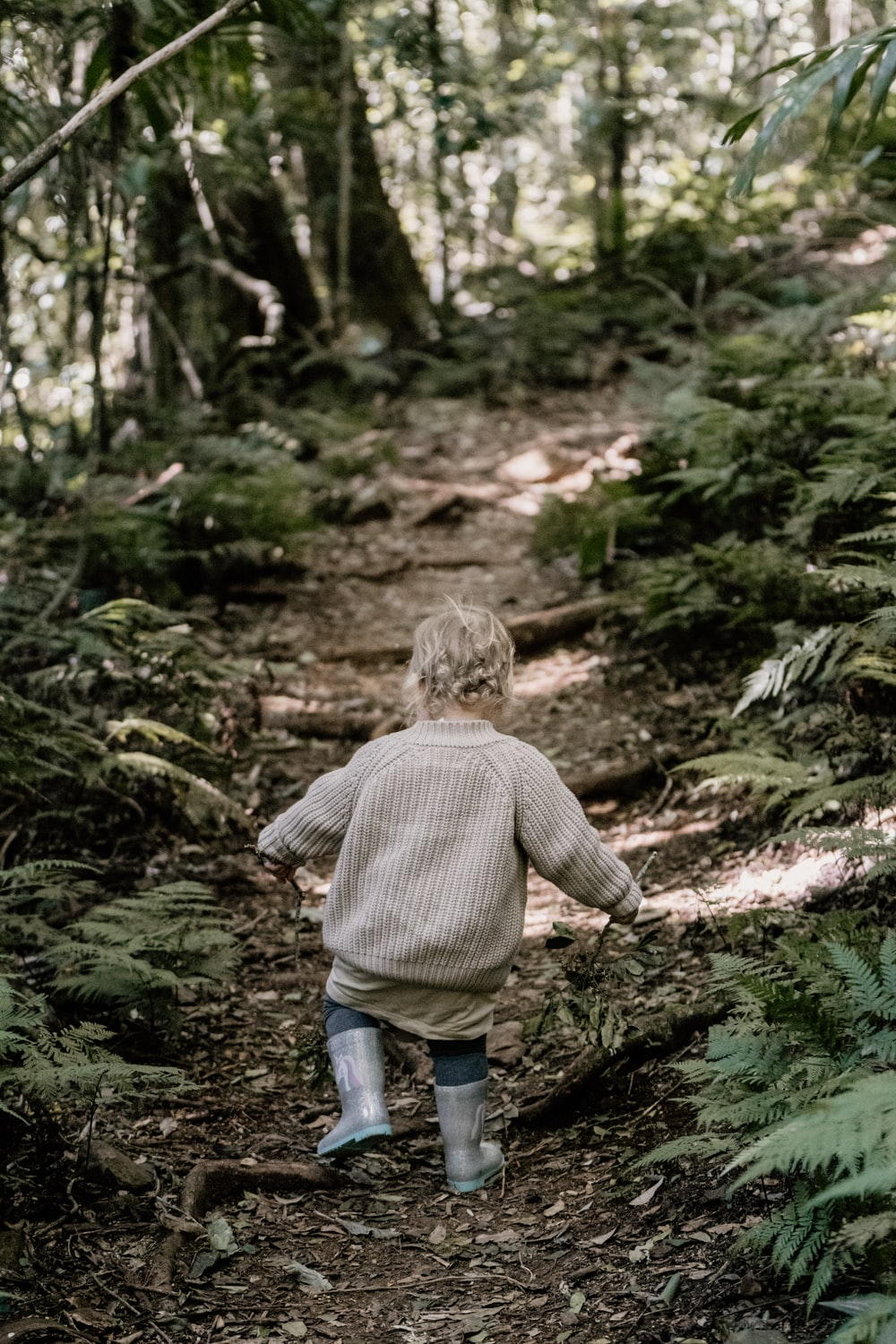 boy in brown sweater and blue denim jeans walking on green grass during daytime