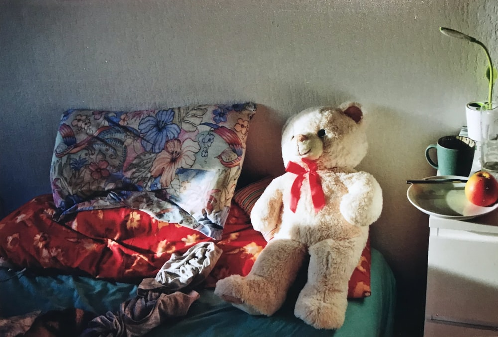 white bear plush toy on red and white floral textile
