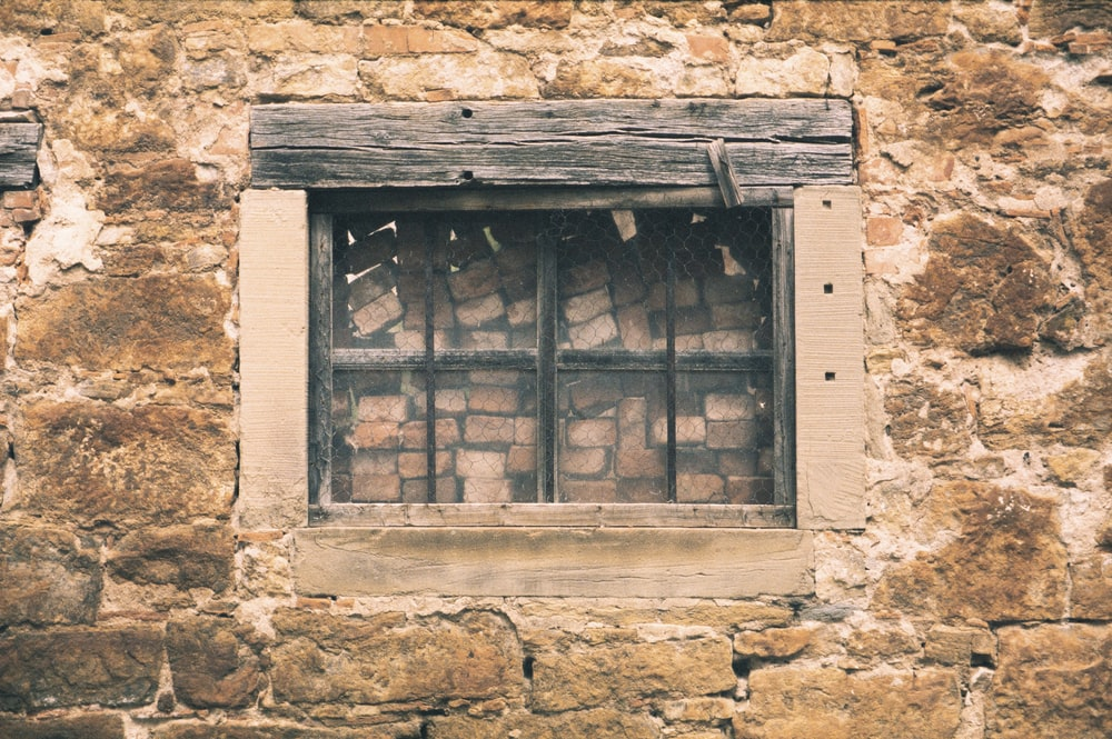 brown wooden window on brown concrete wall
