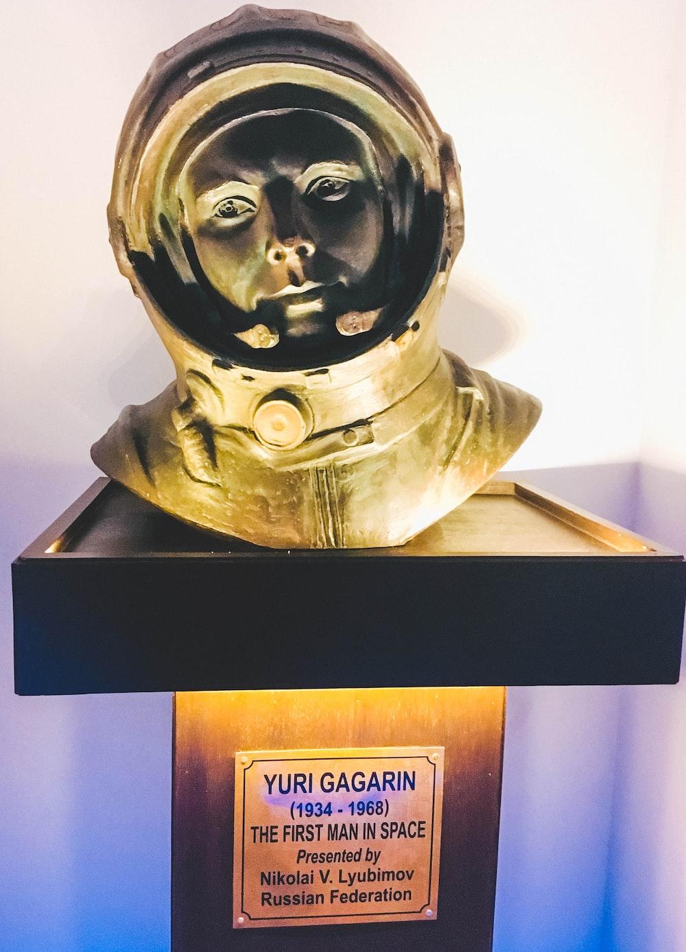 gold human head bust on white wooden shelf