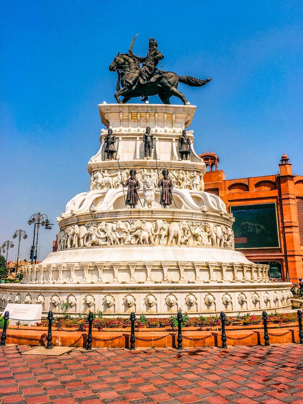 white concrete statue of man riding horse