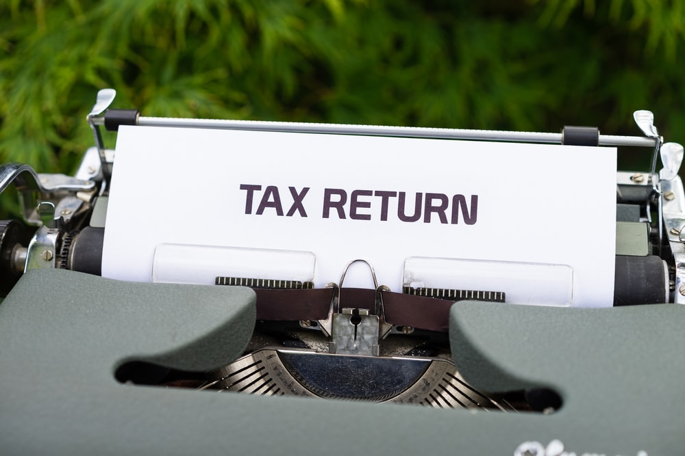 "typewriter shows a printed paper that says ""tax refund"" in all caps"