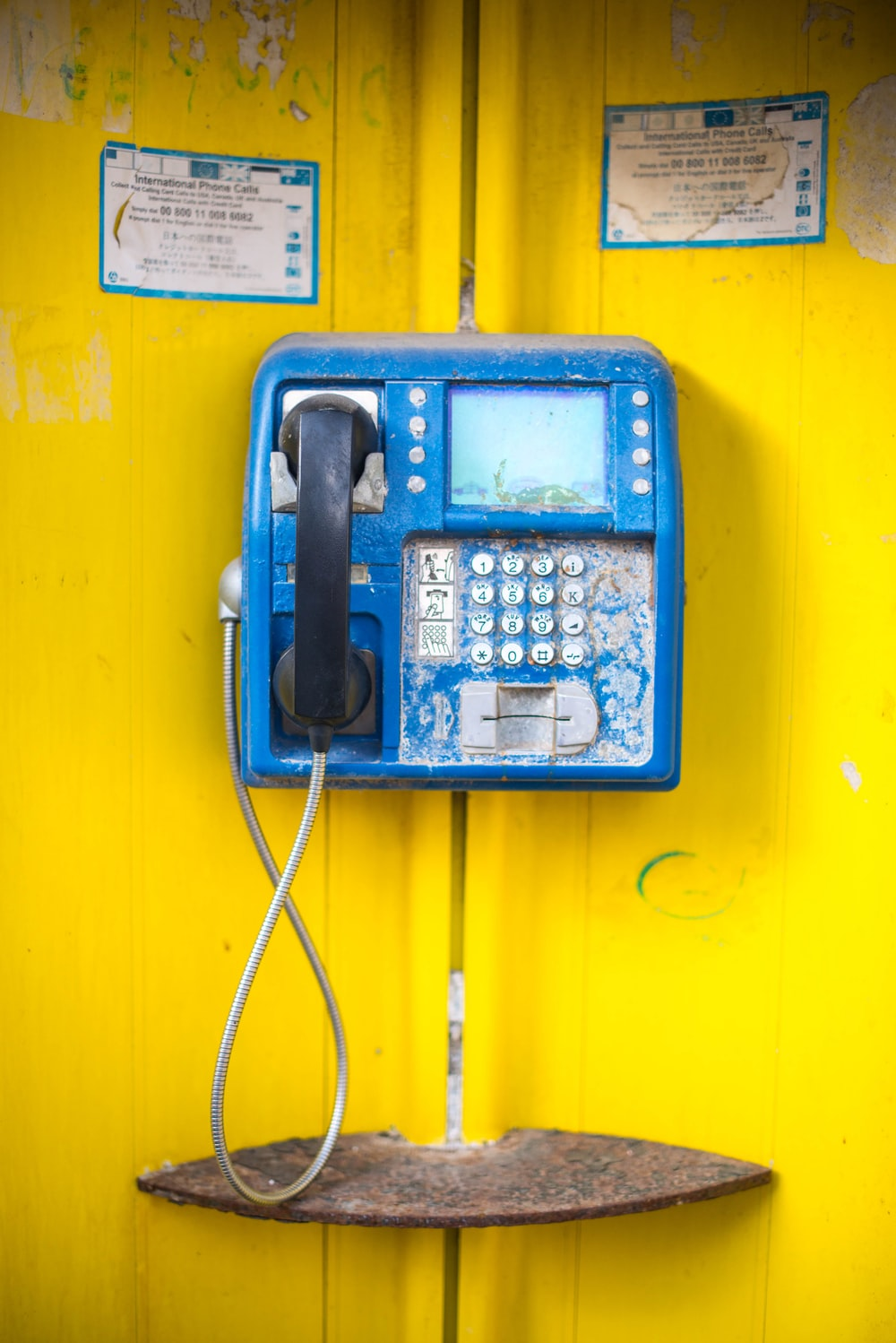 blue and black telephone mounted on yellow wall
