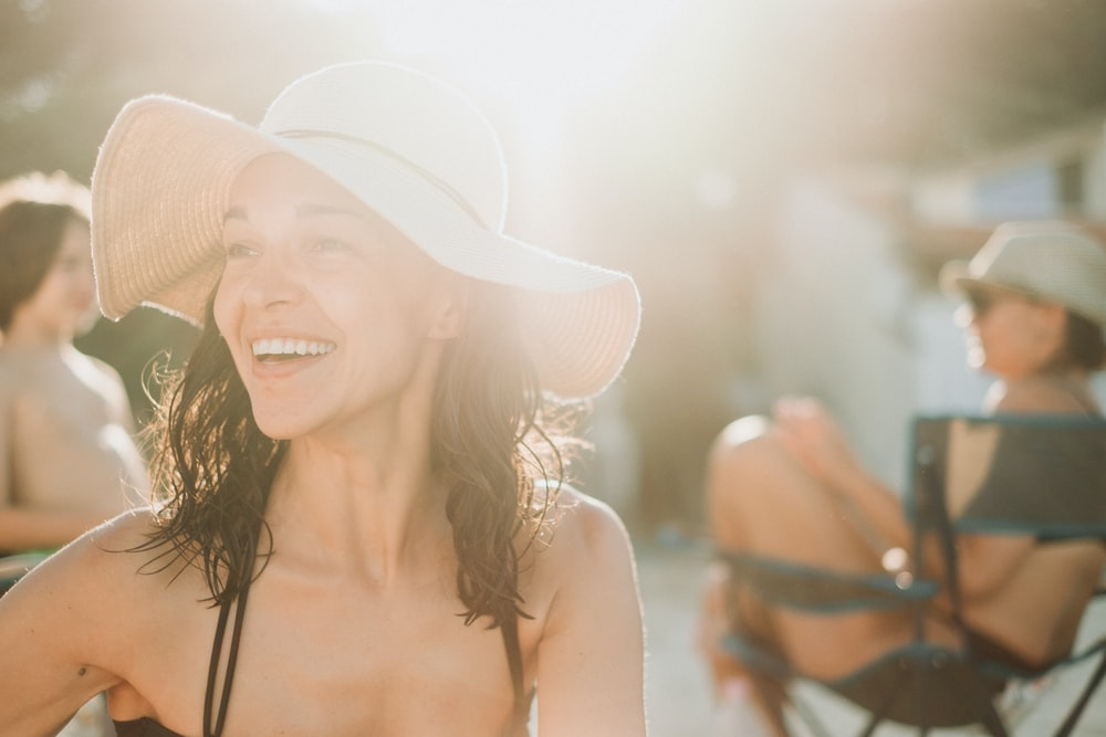 smiling woman in white sun hat