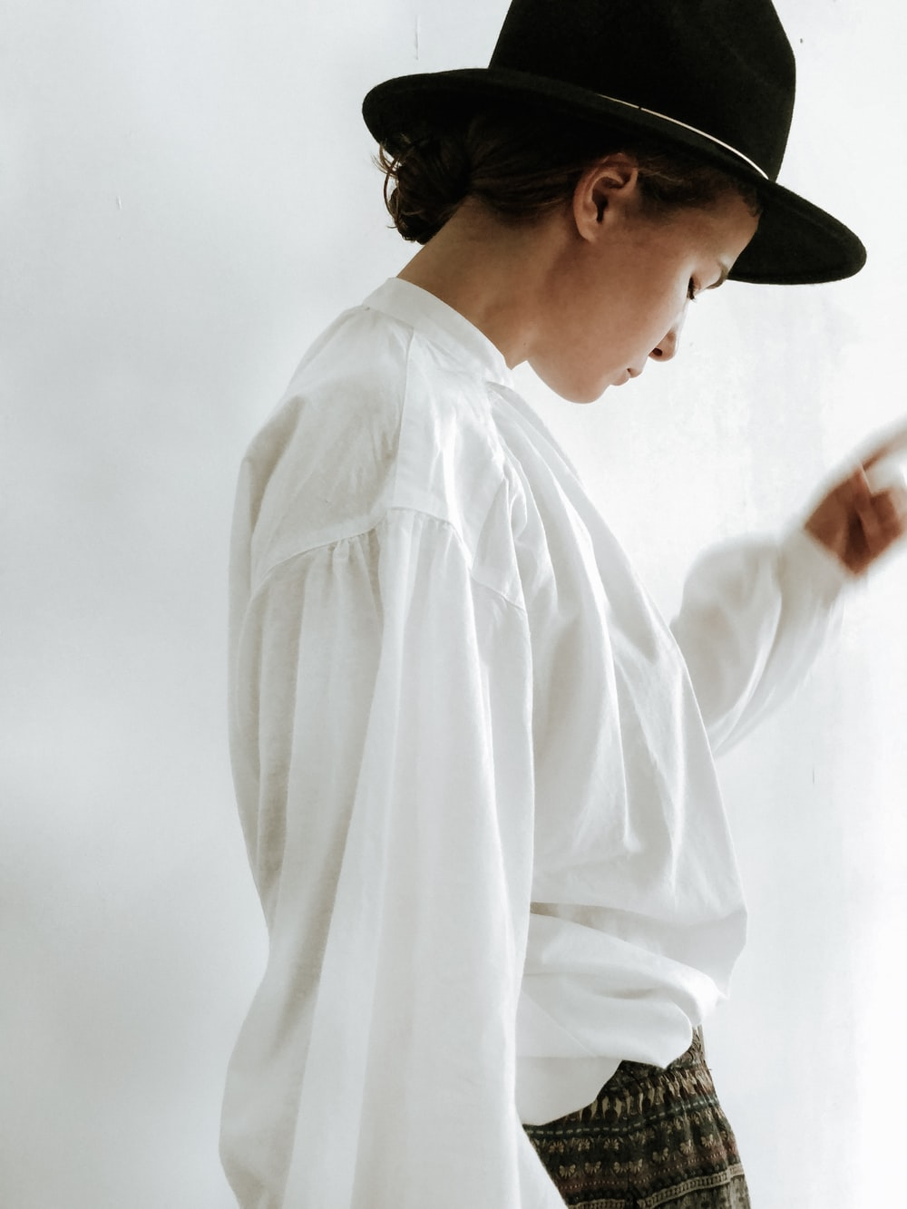 woman in white dress shirt and black fedora hat