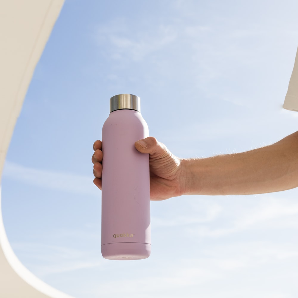 person holding white plastic bottle