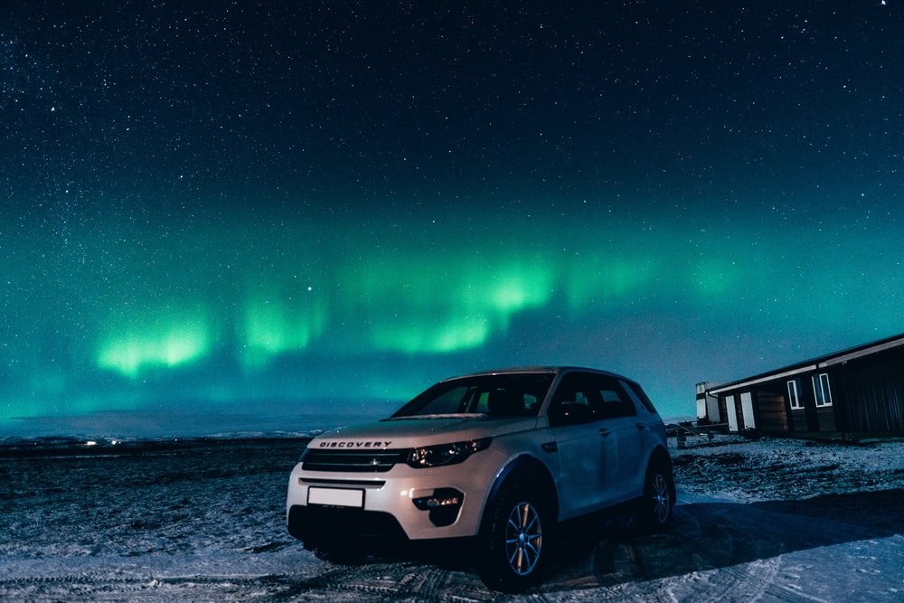 white suv on snow covered ground during night time