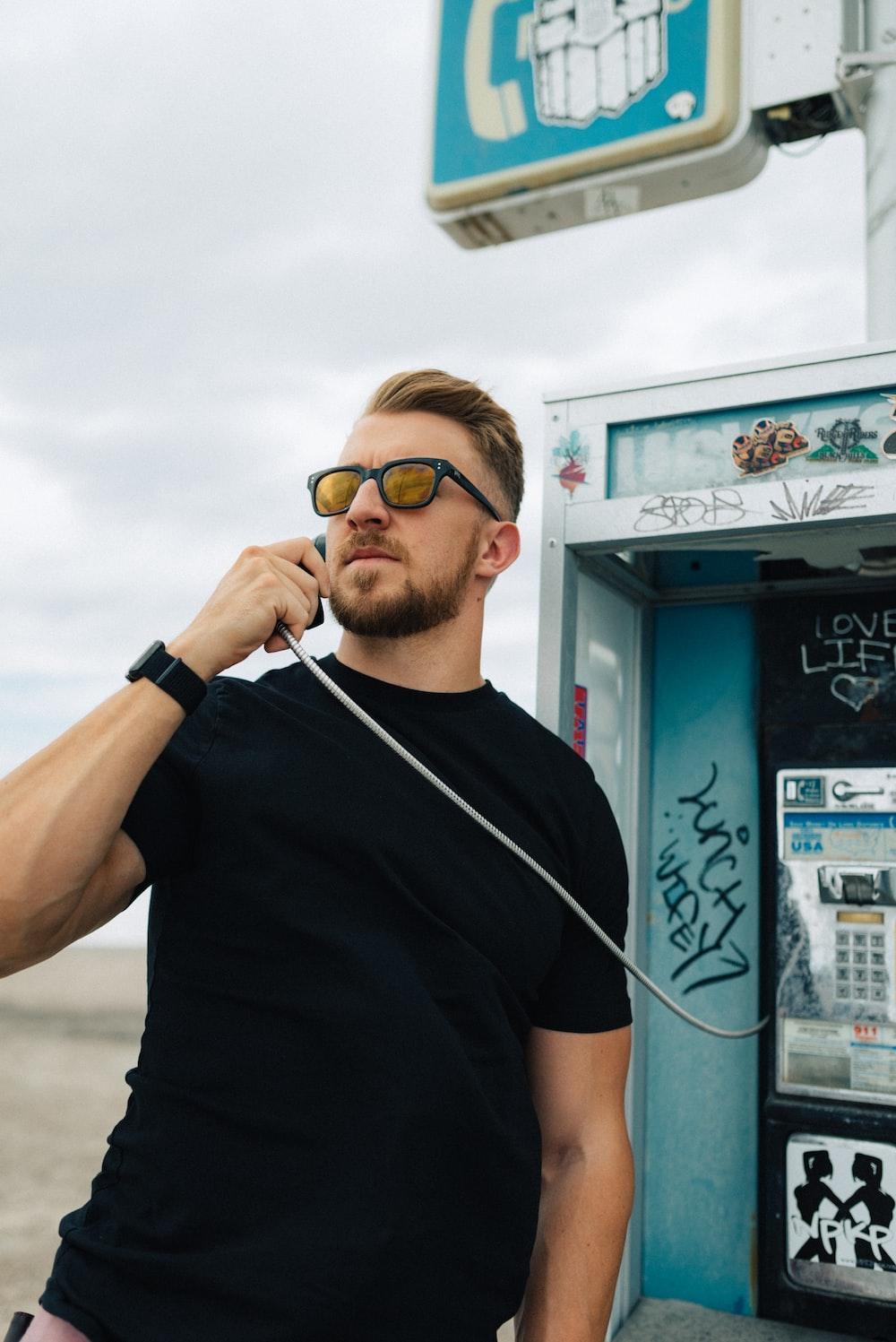 man in black crew neck t-shirt wearing sunglasses