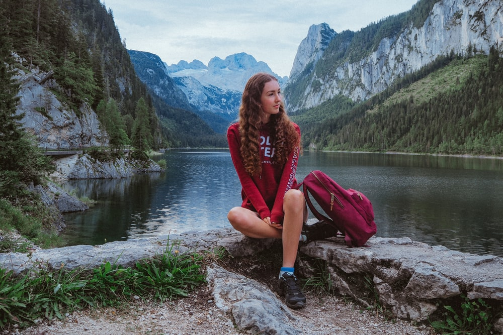 woman in red long sleeve shirt and pink pants sitting on rock near lake during daytime