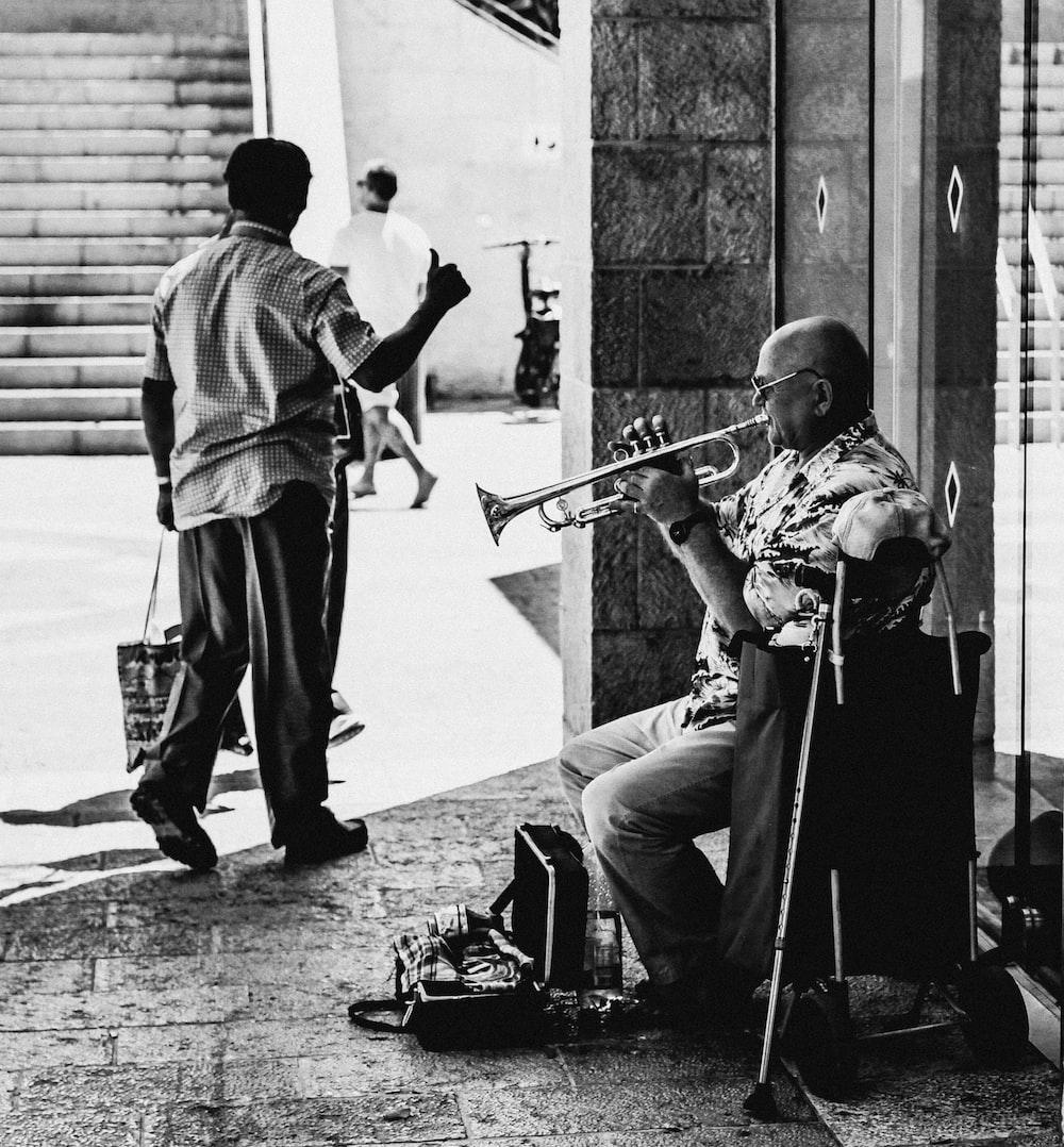 man playing guitar beside man playing guitar