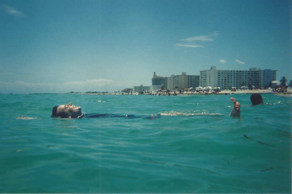 man in blue shorts swimming on sea during daytime