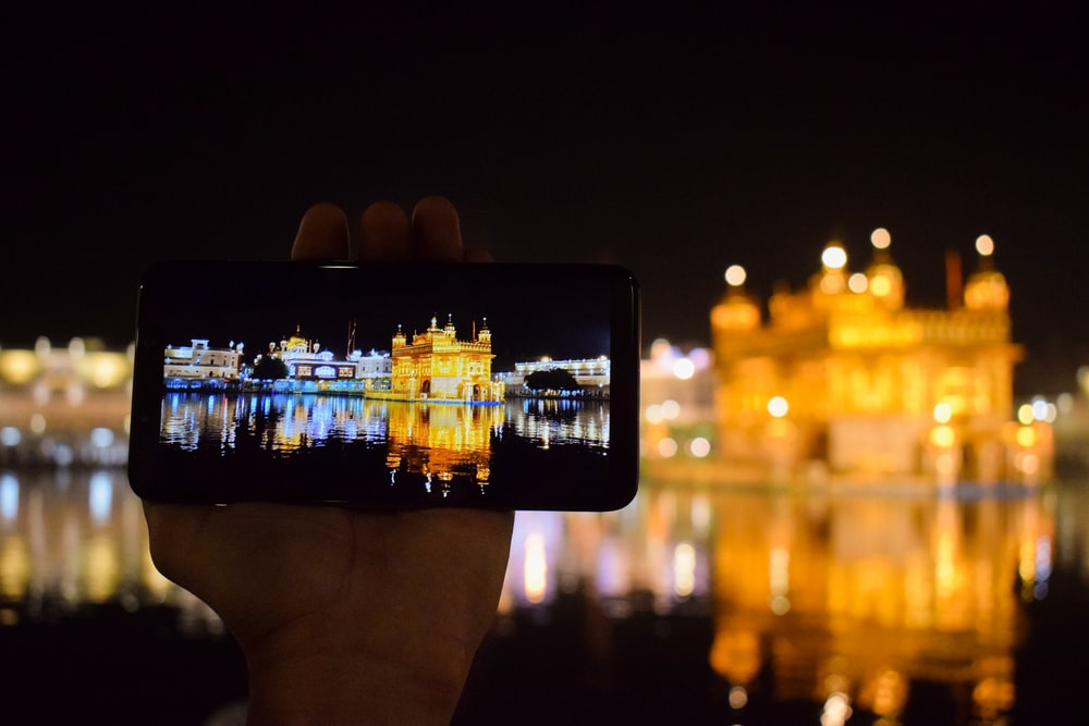 person holding smartphone taking photo of city buildings during night time