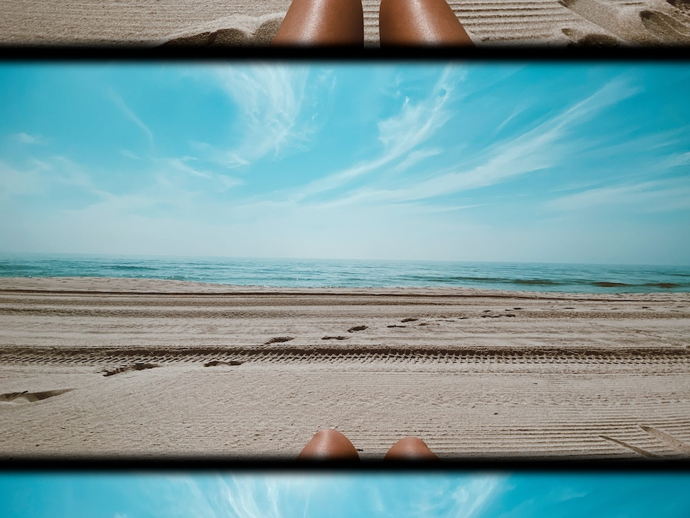 person lying on beach sand during daytime