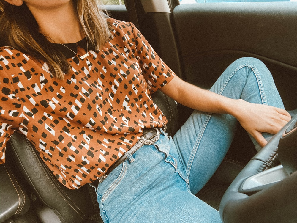 woman in brown and white shirt and blue denim jeans sitting on car seat
