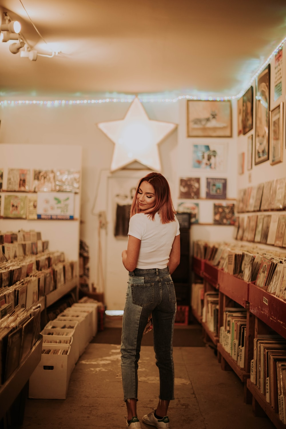woman in white t-shirt and blue denim jeans standing near brown wooden shelf
