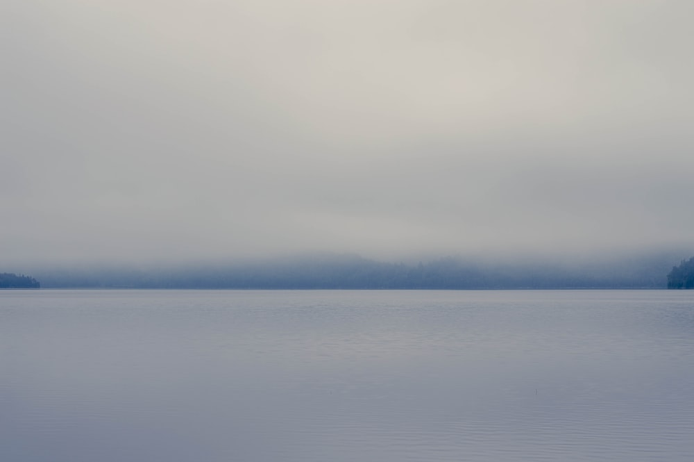 body of water under white clouds during daytime