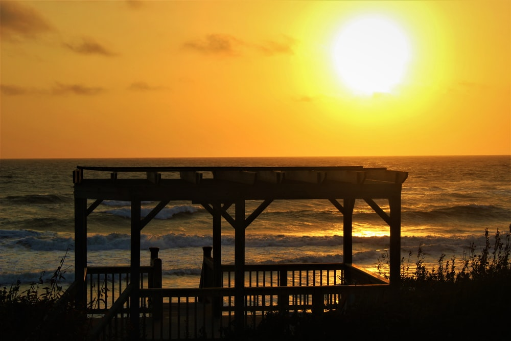 silhouette of person standing on wooden dock during sunset
