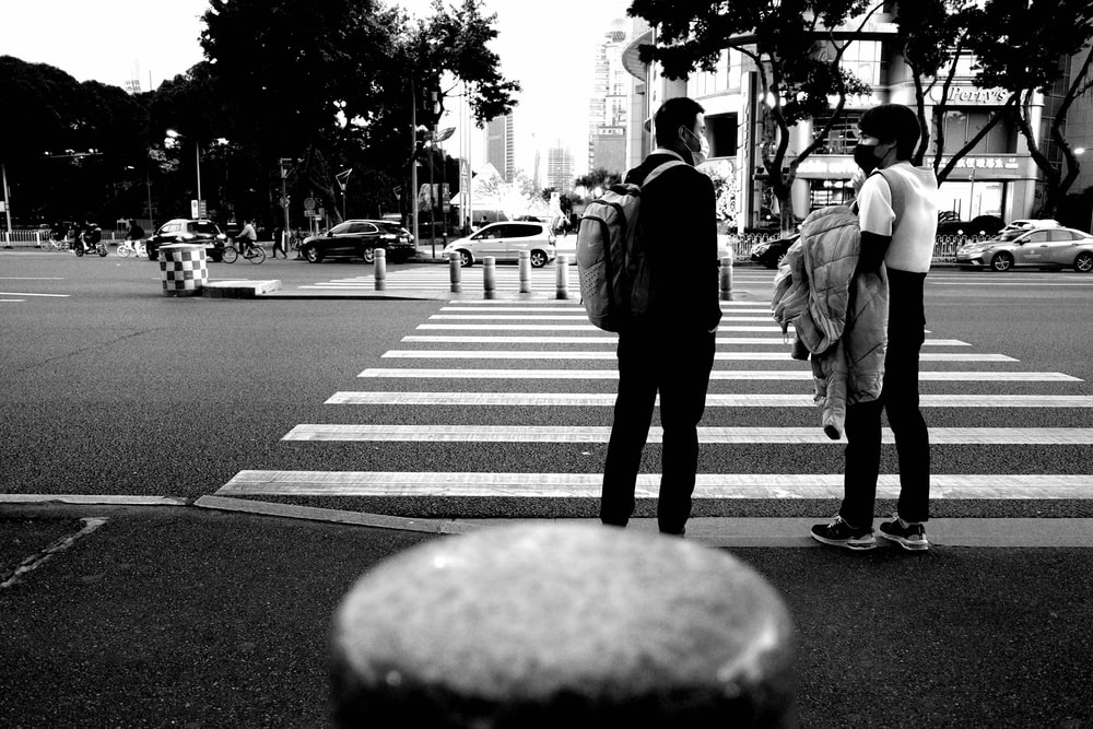 grayscale photo of man and woman walking on pedestrian lane