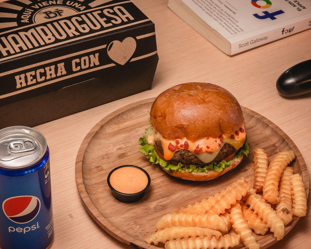 burger and fries on brown wooden table