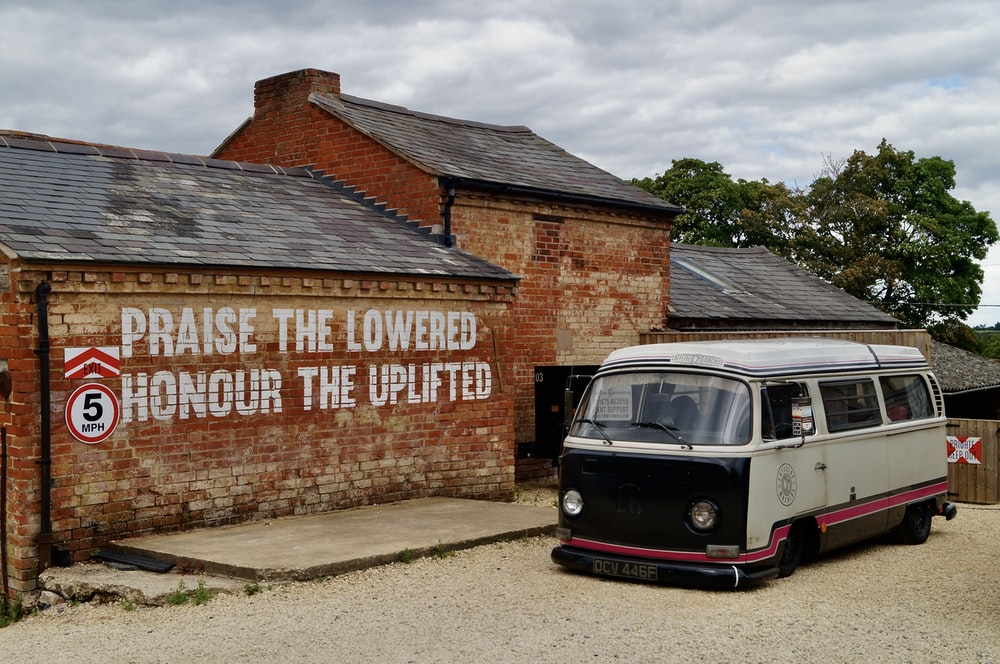 red and white volkswagen t-1 parked beside brown brick wall during daytime