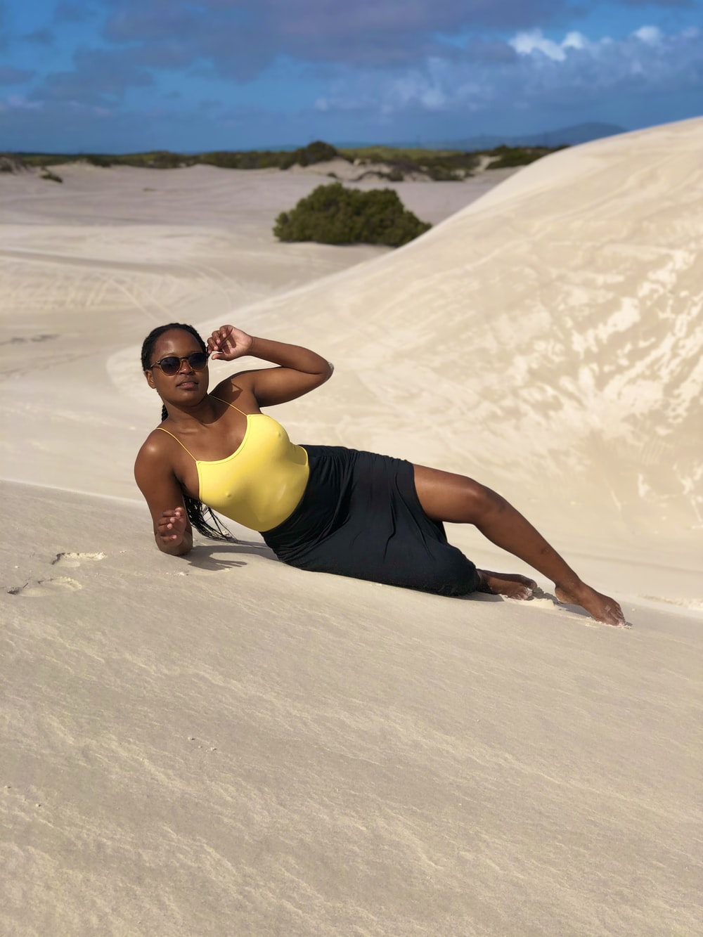 woman in yellow tank top and black shorts lying on white sand during daytime