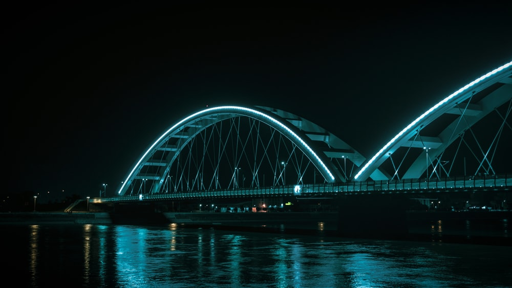 white bridge over body of water during night time