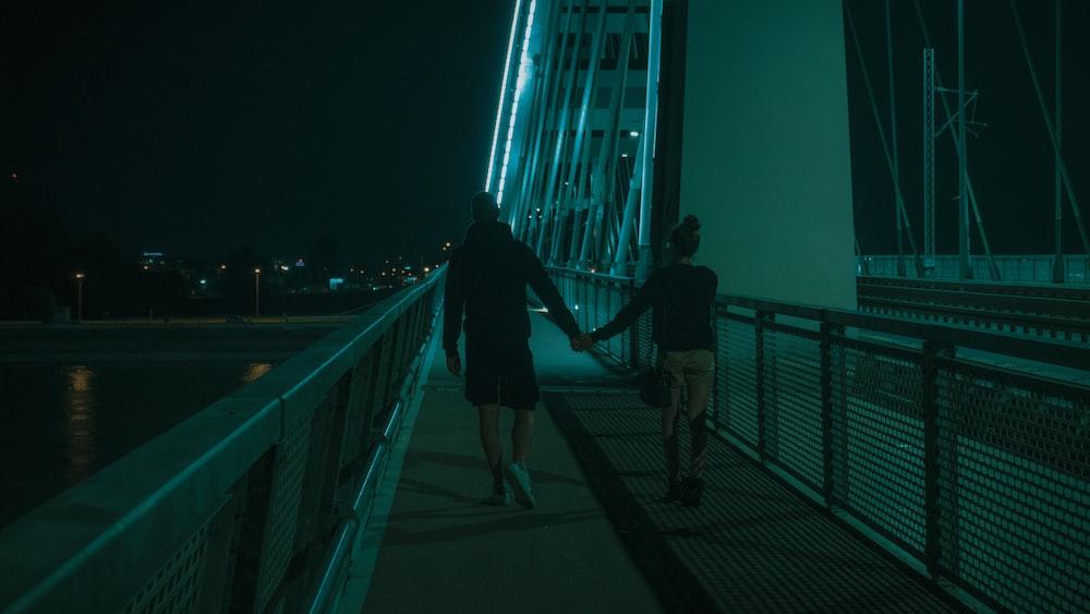 woman in black jacket walking on bridge during night time