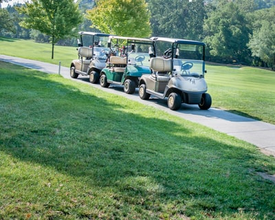 white and black golf cart on green grass field during daytime