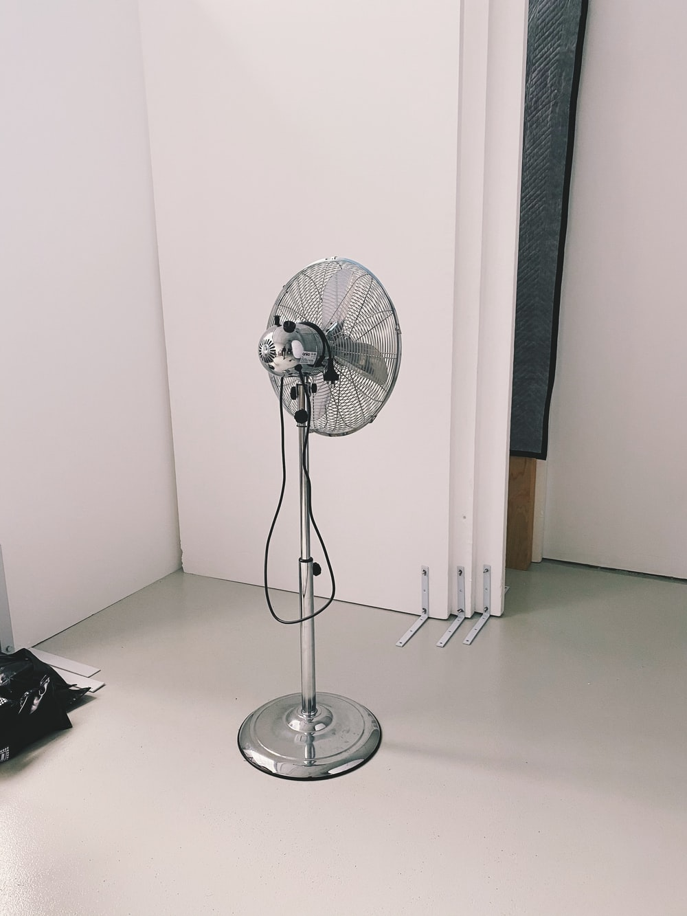 silver stand fan on brown wooden table
