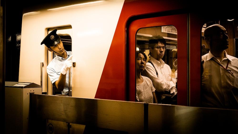 man in white dress shirt and black pants sitting on train seat