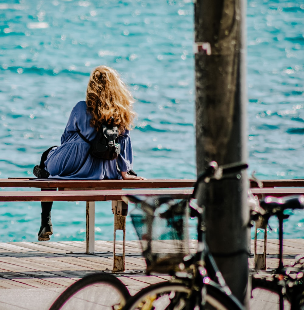woman in black jacket sitting on brown wooden bench beside body of water during daytime
