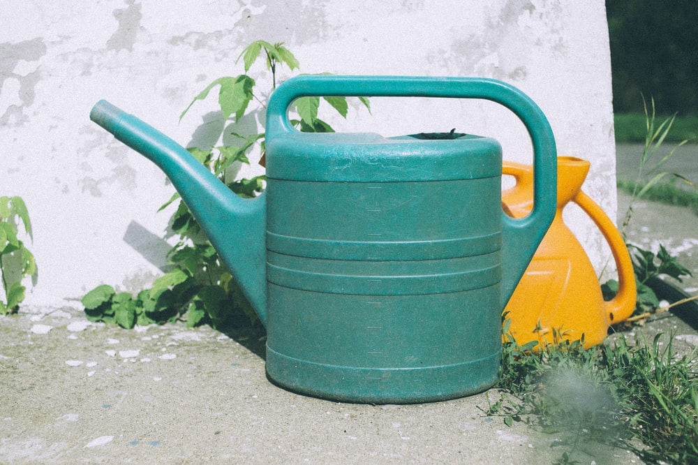 green watering can on gray concrete floor