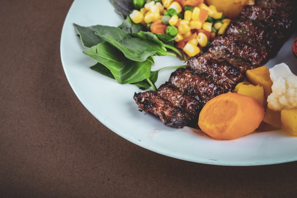 grilled meat with green vegetable on white ceramic plate