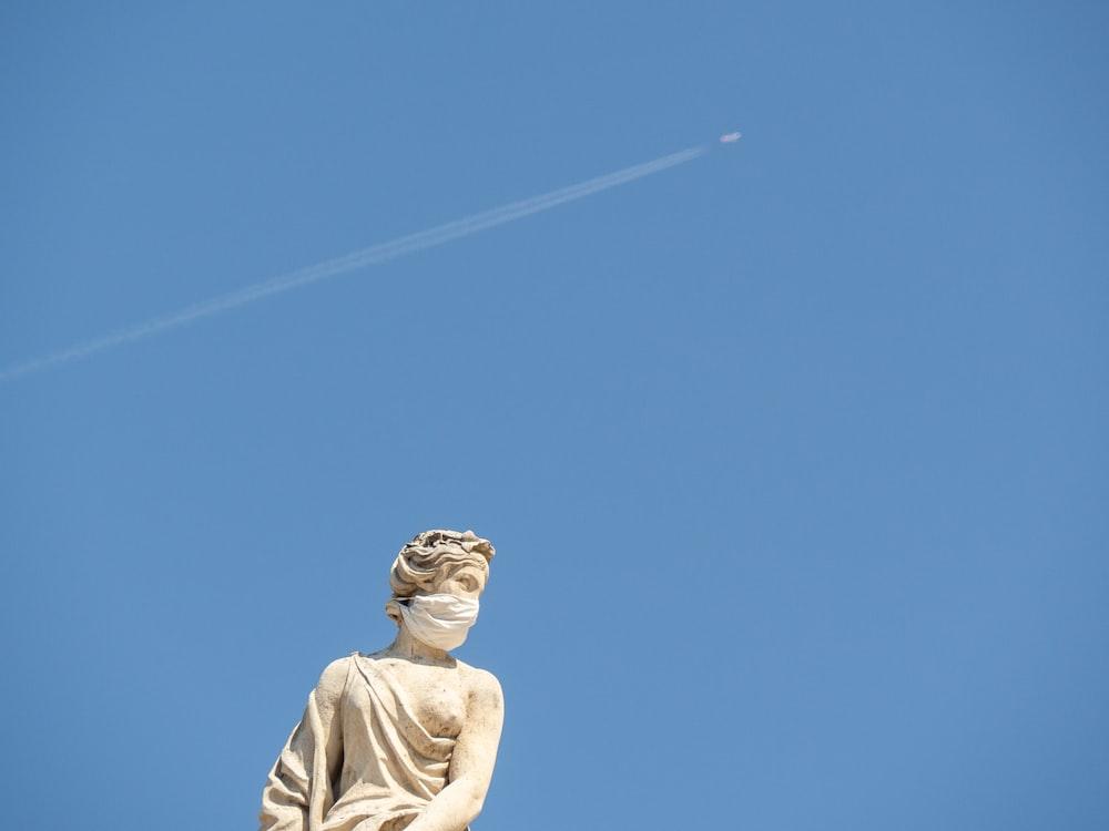 man in white shirt statue under blue sky during daytime