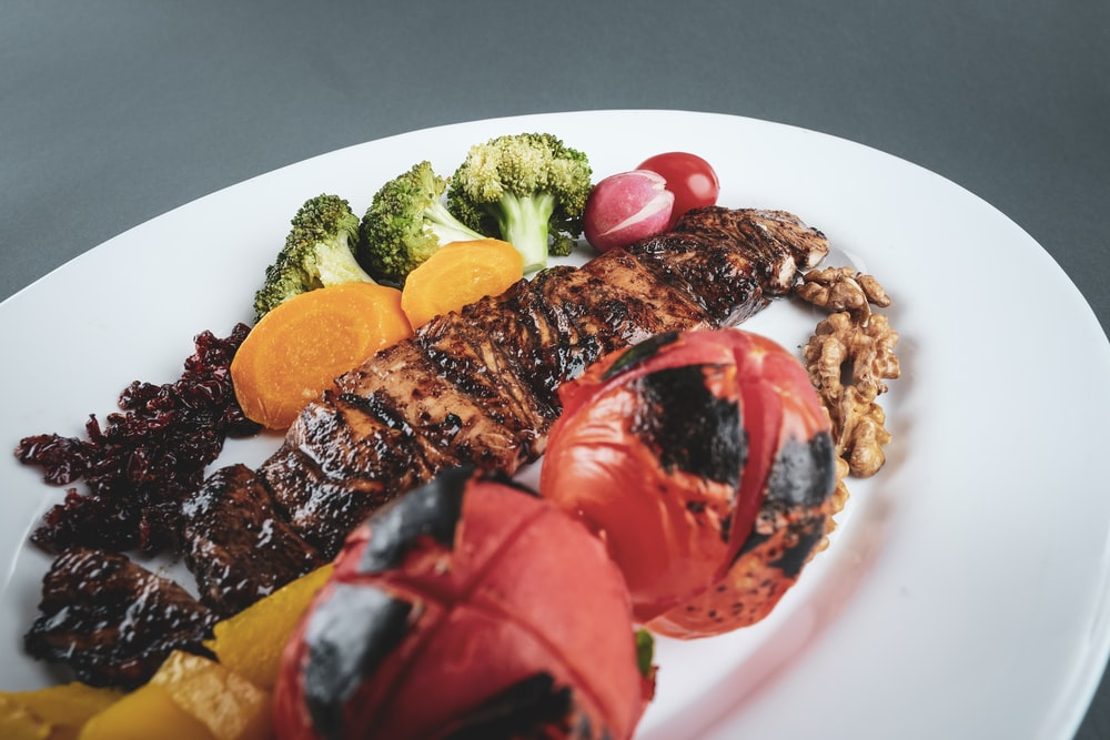 grilled meat with sliced tomato and green vegetable on white ceramic plate