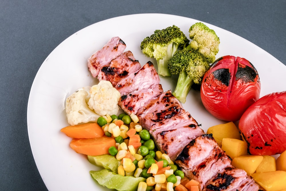 grilled meat with green vegetable and red chili on white ceramic plate