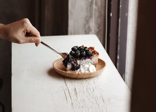 person holding spoon with black berries on it