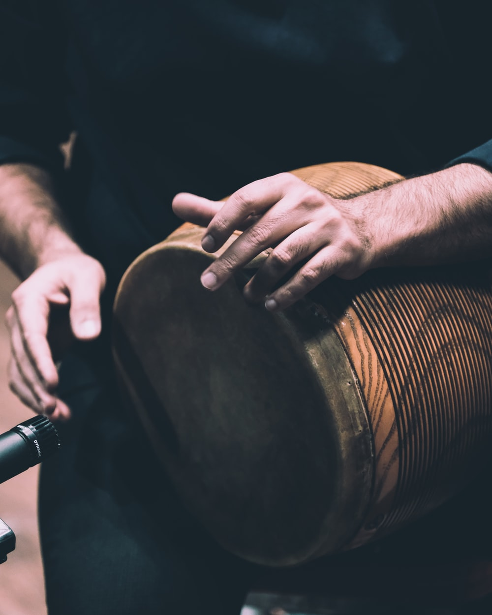 person in black shirt holding brown wooden drum