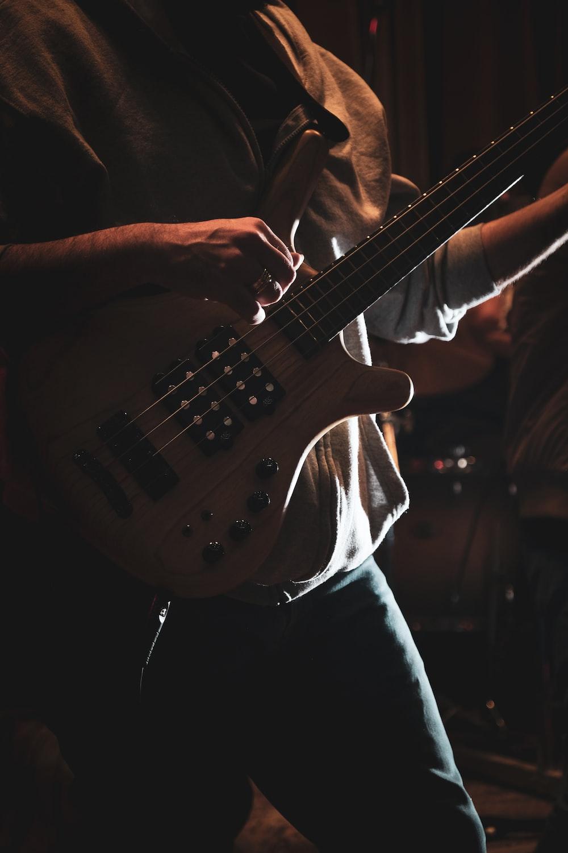 man in white shirt playing electric guitar