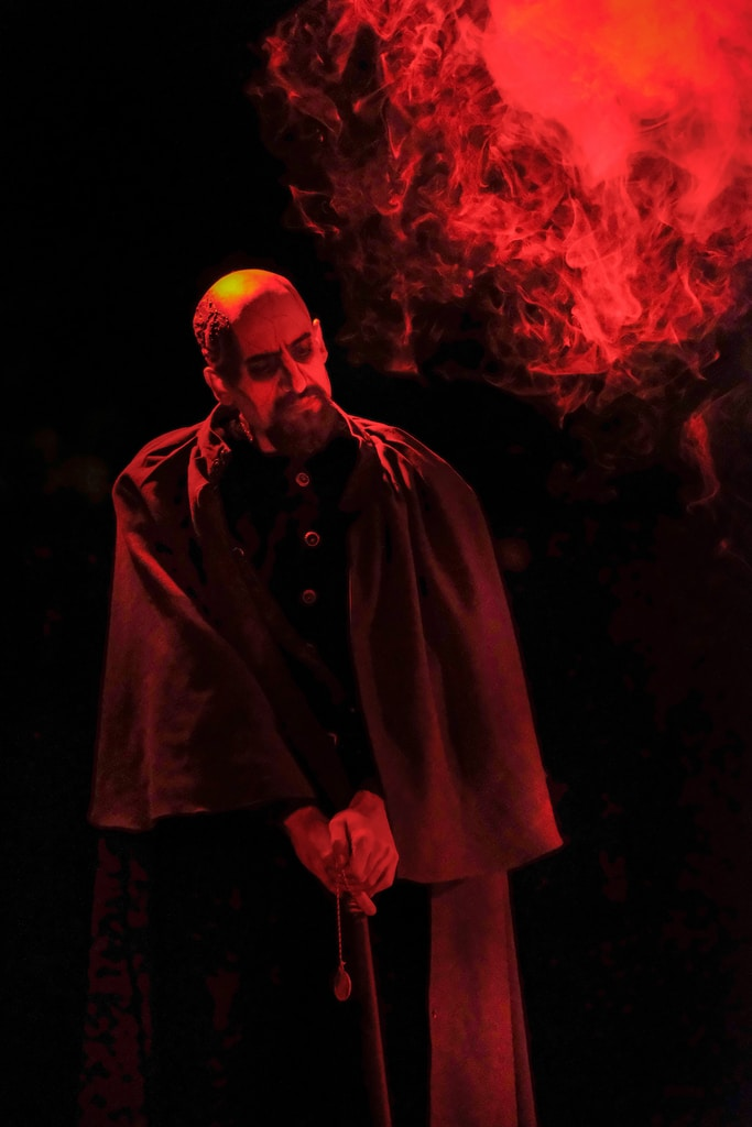 man in black coat standing near red fire