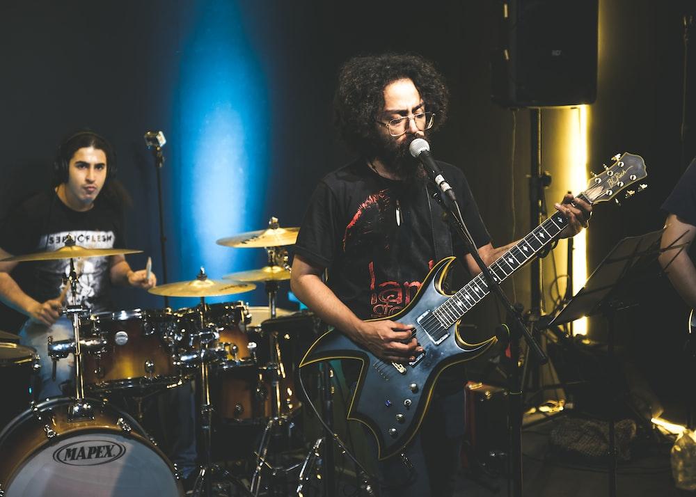 man in black shirt playing electric guitar