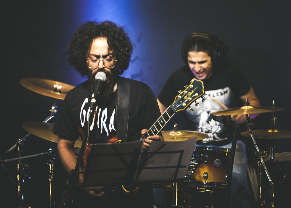 man in black and white crew neck t-shirt playing guitar